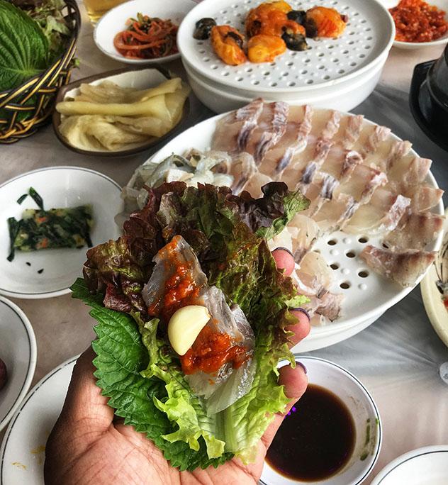 Un rollito: el 'hoe', o pescado crudo, se puede envolver con una hoja de lechuga y aderezar con salsa y ajo, Busan, Corea del Sur © MaSovaida Morgan / Lonely Planet