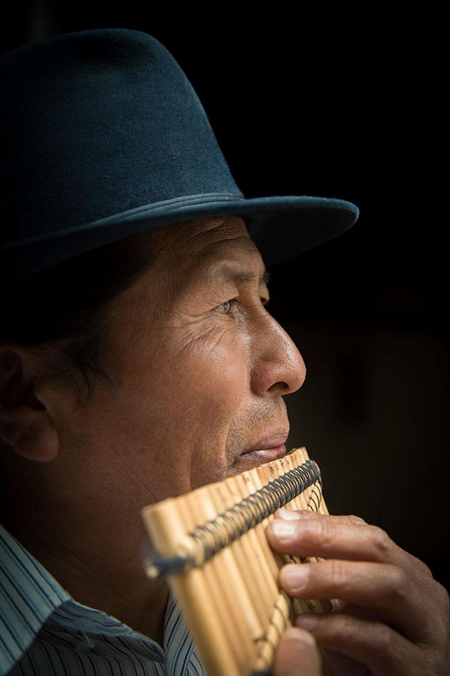 Jose Luis Fichamba toca un rondador de bambú recién fabricado en su taller, Ecuador © Philip Lee Harvey / Lonely Planet