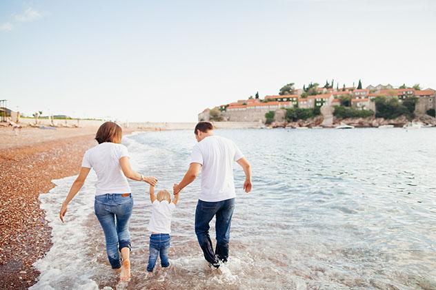 Familia viajera disfrutando de la costa © shevtsovy / Shutterstock