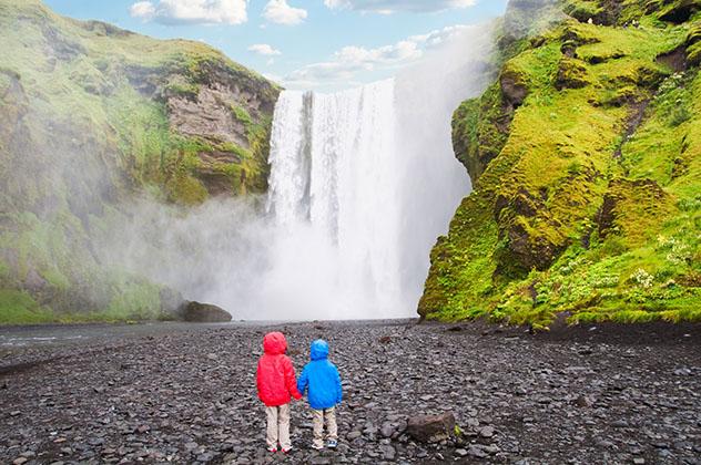 Aventuras en familia: niños ante la cascada de Skogafoss, Islandia