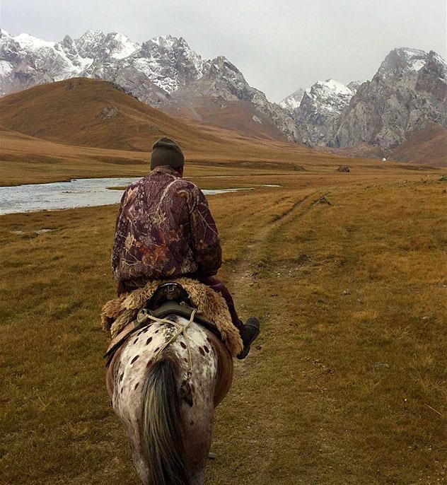 A caballo hacia el lago Köl-Suu: nuestro guía nos conduce por las montañas, Kirguistán © Megan Eaves / Lonely Planet