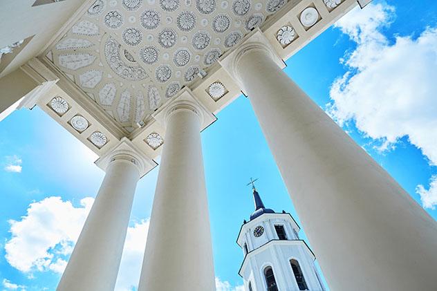 El campanario de la catedral de Vilna visto entre sus columnas clásicas, Lituania © Ekaterina Pokrovsky / Shutterstock
