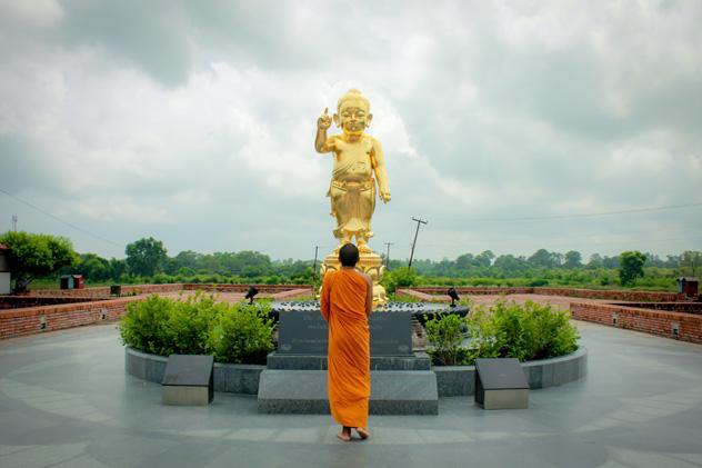 Monje frente a la estatua de Buda en el templo Maya Devi, lugar de nacimiento de Siddhartha Gautama, Lumbini, Nepal © Photohipster / Shutterstock