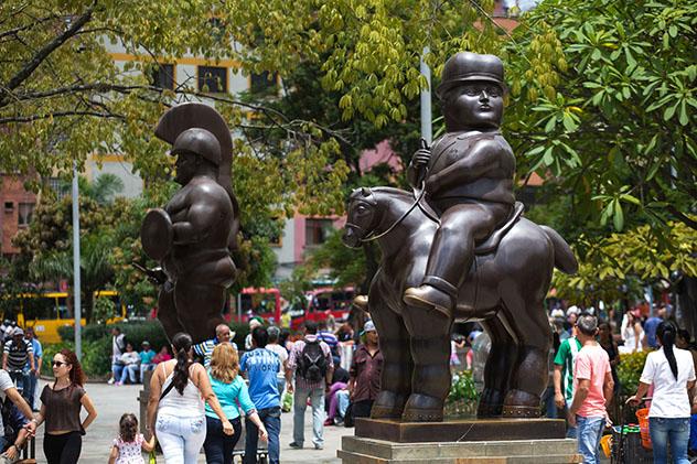 Turismo sostenible: comunidad. Una multitud entre esculturas de Fernando Botero, Medellín, Colombia
