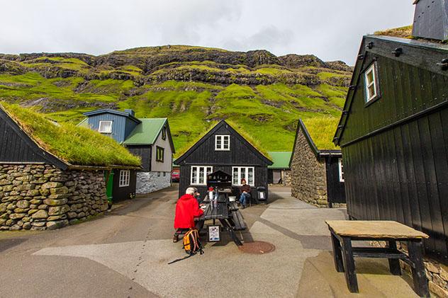Turismo sostenible: comunidad. El puesto de gofres y café, con dos clientes, en Tjørnuvik, islas Feroe