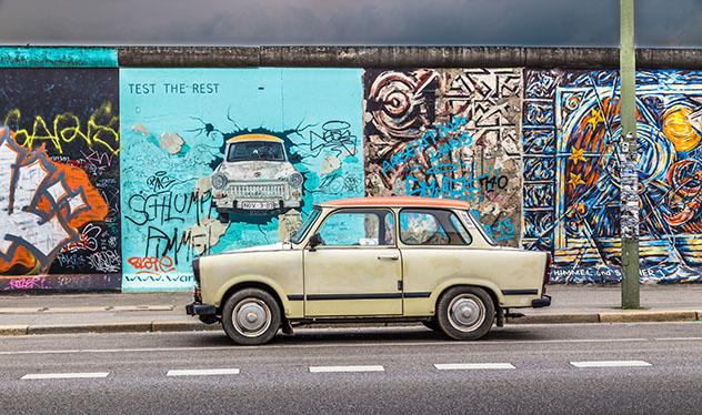 Turismo sostenible: comunidad. Un antiguo Trabant aparcado frente al Muro de Berlín en la East Side Gallery