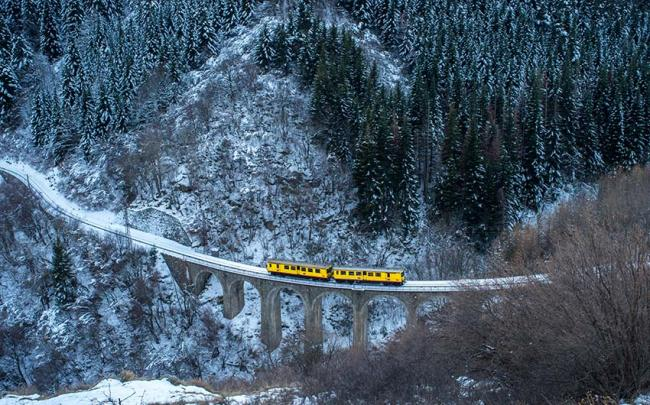 Tren amarillo atravesando el viaducto Séjourné, Francia